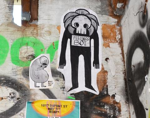 feelings boi pasteup beside a pot belly pop pasteup on a wall