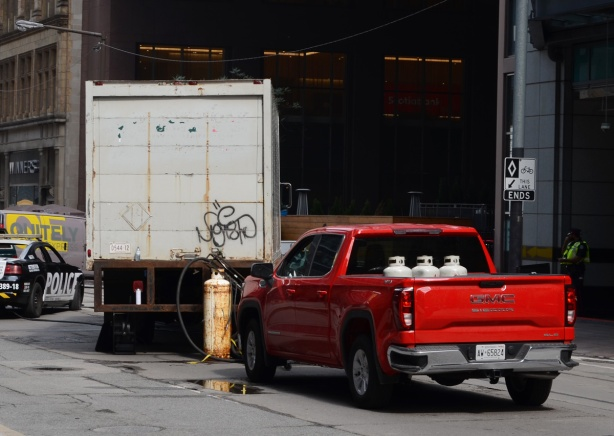 part of a film set on Adelaide, a red pick up truck with propane tanks in the back, with another tank wired to the back of a white panel truck