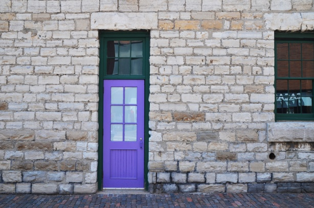 a purple door on a grey limestone wall, distillery district