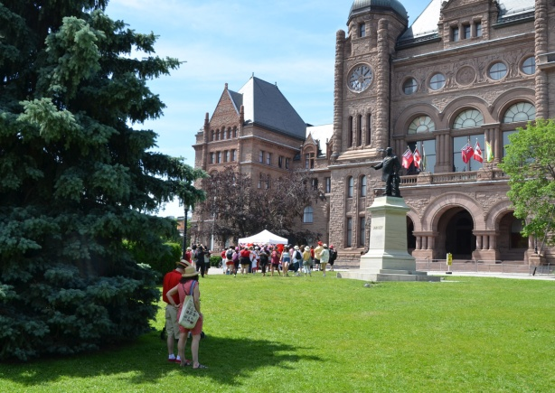 front of Queens Park buildings, parliament buildings, on the grass a couple stand by a tree, looking at group under a tent, Canada Day celebrations
