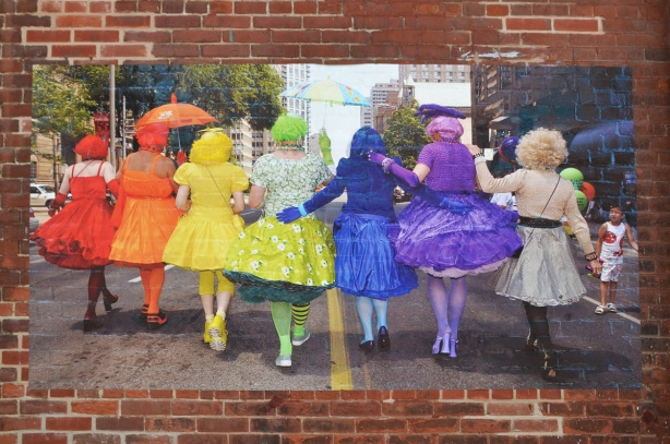 a large picture pasted to a brick wall, the backs of 6 drag queens each in a different colour outfit, making a rainbow when seen from the back