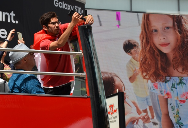 a red head girl in a large advert on a building beside a man in red adjust a microphone on the top of a red double decker tourist hop on hop off bus
