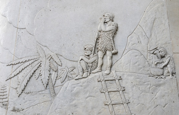 relief sculpture in concrete on exterior of wall, cavemen scene, with palm trees, three people dressed in animal skins. One is cooking - stirring with a stick in a large pot over a fire, one is standing and shouting with hands cupped around his mouth. A ladder made of wood pieces lashed together leans against a rock