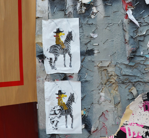 two copies of a small pasteup of a yellow figure riding a zebra