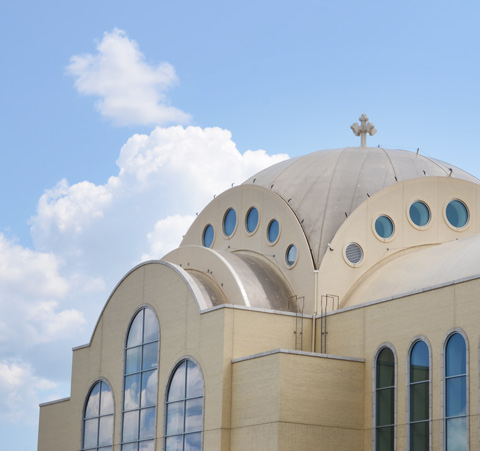 dome of very large pale brown cathedral church, St. Marks Coptic Church, new building, against the blue sky with a few puffy white clouds