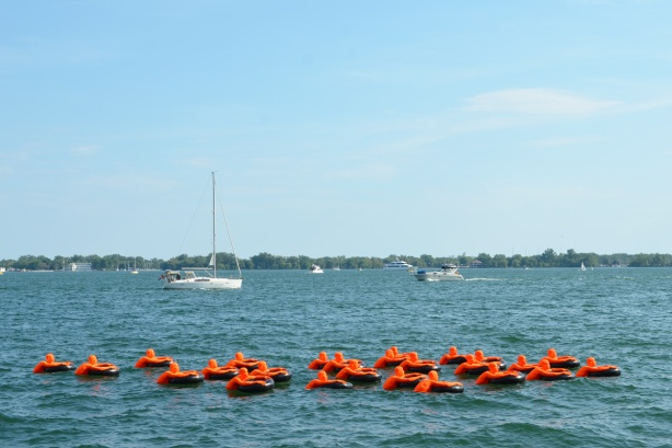 two small boats on Lake Ontario, Toronto harbour, pass by the art installation S O S or Safety Orange Swimmers