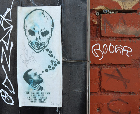 pasteup on a wall, of a skull looking down at a man's head, who is looking up at skull, Letters are between the two mouths. words written below the man