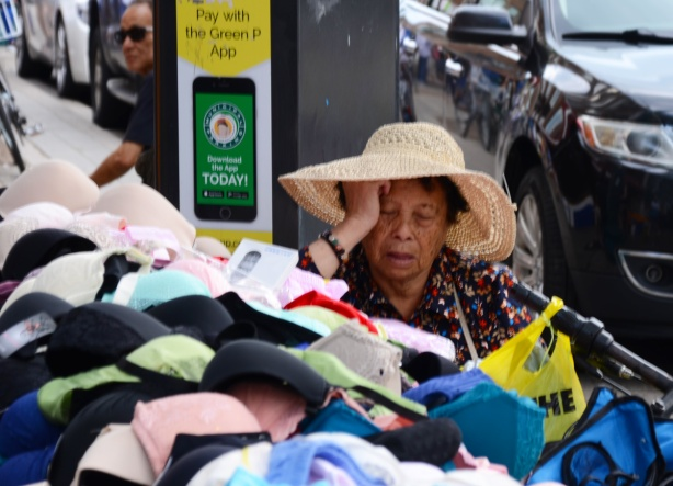 an older Chinese woman in a wide brimmed straw hat falls asleep sitting beside a table of bras that she is helping to sell