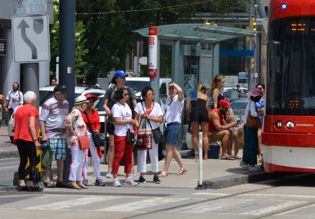 a crowd of people at a TTC stop on Queens Quay