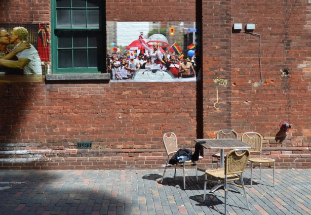 pictures on a brick wall, above a table with empty chairs, outdoors,