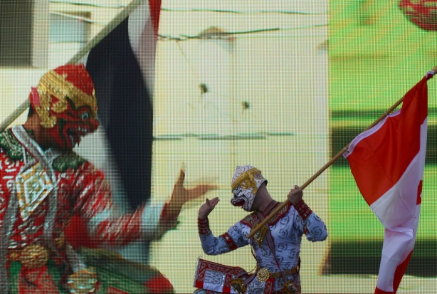 a man in Thai costume and holding a Canadian flag does a Thai traditional dance on the stage at Yonge Dundas Square. behind him a video of another dancer is playing on a large screen