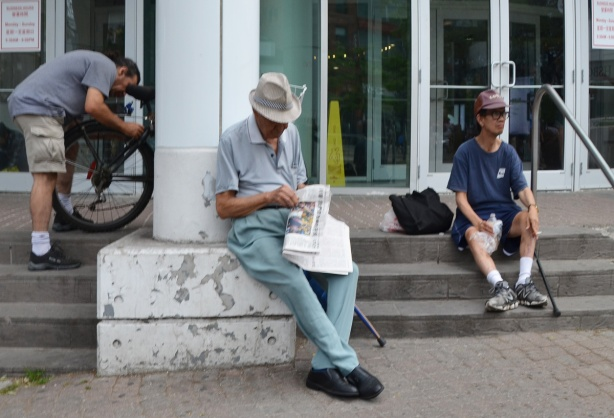 three men sitting on the steps, one unlocking a bike, another reading a newspaper and the third just sitting