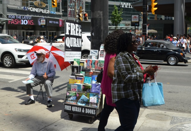 two black women walk past a man sitting in a chair with a large red and white Canadian flag umbrella. he is giving away free quran books on the sidewalk by Yonge street, traffic passing by on the street behind them