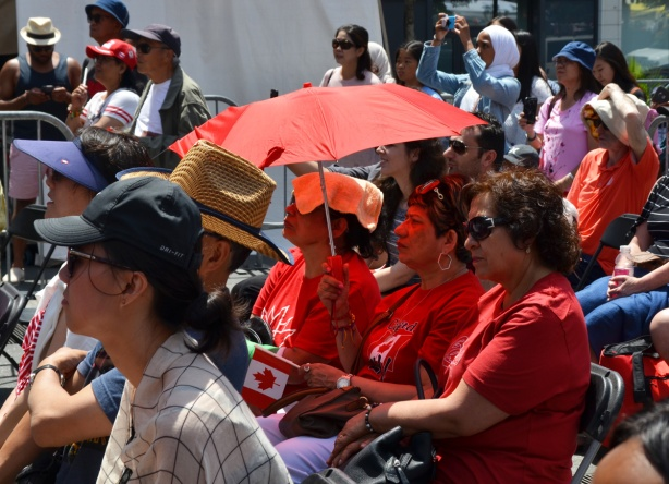 three women in red under a red umbrella watching a Canada day celebration