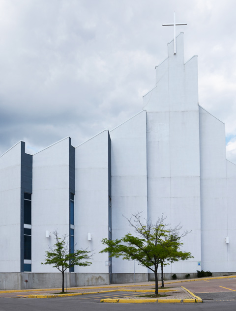 part of front of modern white church with skinny vertical windows and a white cross on top, two small trees in front