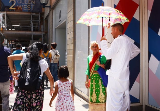 a man in long white robes holds an umbrella as he stands on the sidewalk talking to a woman in Southeast Asian clothing