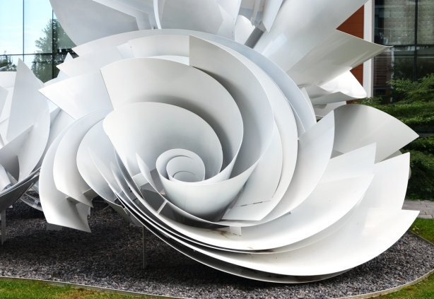 part of a large sculpture, sheets of white material curve and join together like the shape of a rose