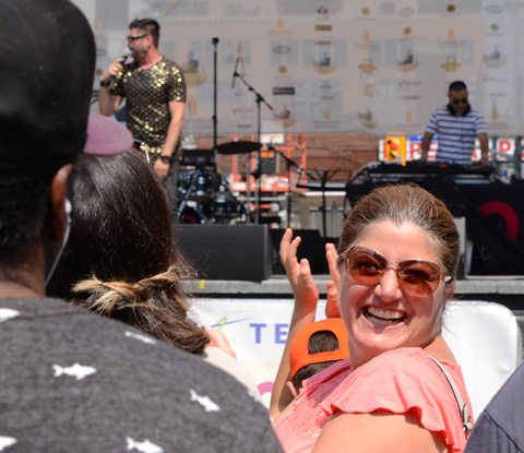 woman in a pink top and sunglasses turns her head towards the camera with a big smile, behind her is a performance on a stage and a man in an orange baseball cap clapping with his hands above his head, at Yonge Dundas square Taste of the Middle East festival