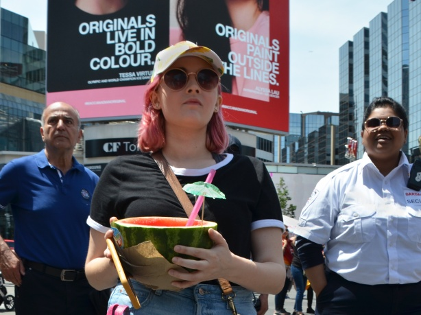 a woman weth pinkish hair carried a half watermelon with a straw and a little green paper umbrella in it, she is the middle of three people standing in Yonge Dundas square