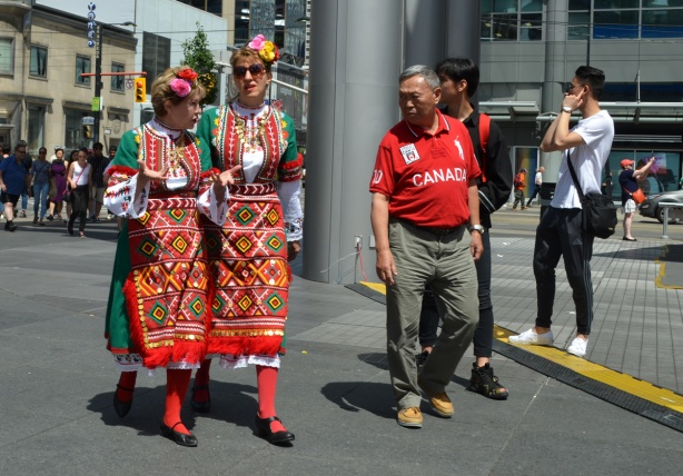 two womenin national costume, or traditional clothes of another country, walk through Dundas Square, an Asian man is looking at them with a strange look on his face