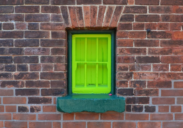 bright lime green window with dark green window frame, brick wall