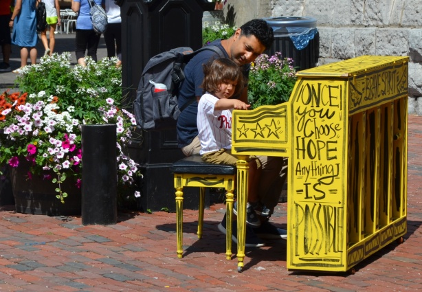 a father and daughter playing a piano, outside, piano is painted bright yellow and the words Once you choose hope anything is possible