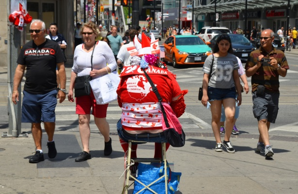 four people walk past a man sitting on a stool, all dressed in red and white with flags and Canadiana