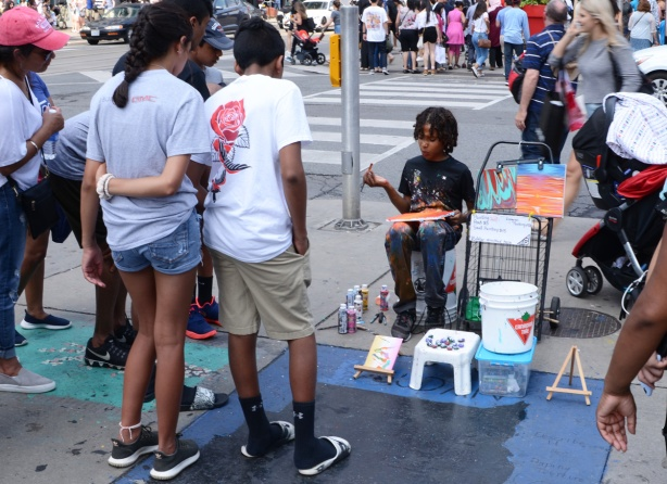 a young black boy sits on a chair at Yonge and Dundas and paints small pictures while people stop to watch him