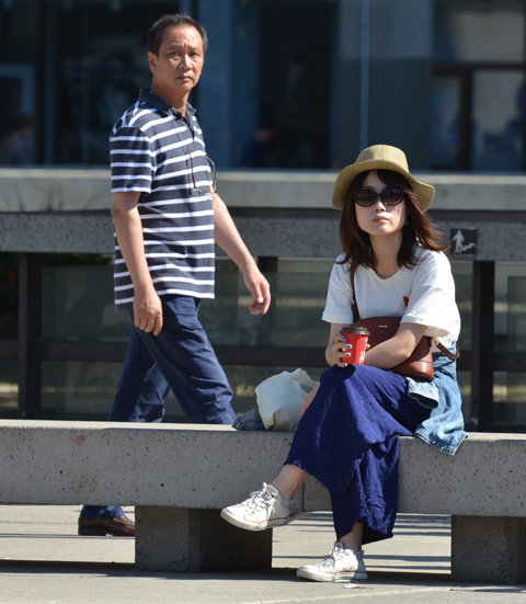 a young Asian woman in a wide brim hat and large sunglasses sits on a concrete bench at Nathan Phillips square as a man walks behind her