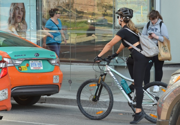 a woman in black on a bike is stopped for a red light in front of a bus shelter. A woman in blue is walking past on the sidewalk, reflections in a store window, a woman in a grey U of T hoodie stands beside the bus shelter. two orange and green taxis are in front of the bike