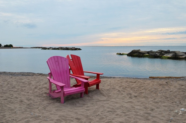 two muskoka chairs, a red muskoka chair and a pink muskoka chair on the beach near the shore of Lake Ontario, Kew beach, sunrise with a few clouds in the sky