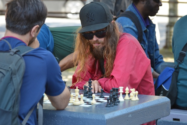 two men playing chess outside. One man has very long hair and is wearing a red shirt and a black baseball hat an dark sunglasses