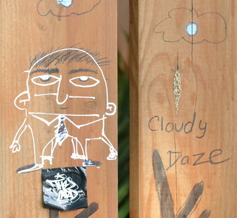 on a wood fence, a drawing in white pencil of a man in a tie, beside him are the words cloudy daze.  above him are two clouds
