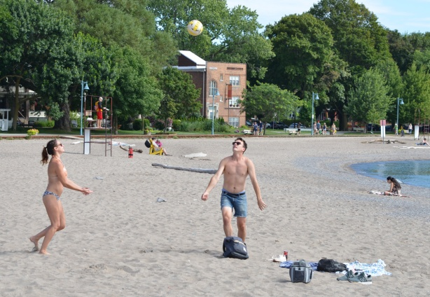 a couple on the beach playing with a volleyball