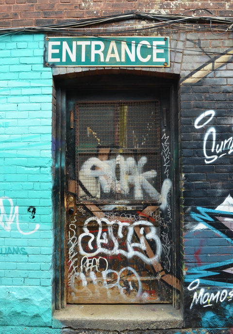 old dark door with entrance sign over the top, with lots of graffiti on the door, mural painted on walls beside the door