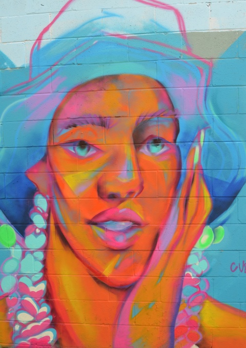 large face mural on an exterior wall in an alley, in bright fluorescent oranges and blues, wearing a large floppy hat