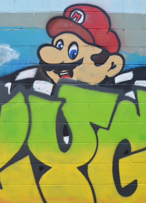 head of Mario from the Nintendo game peaks over the text graffiti