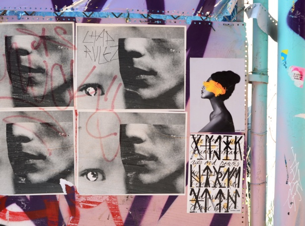 six paper paste up graffiti pieces, four with mens faces in profile with top of head missing but eye beside the chin, one with black woman in profile with yellow over her face, and one with words and symbols