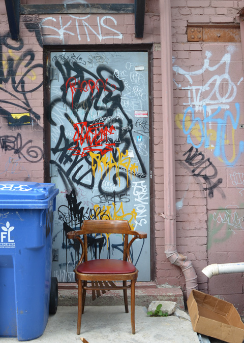 pale blue door with graffiti on it, a blue rubbish bin and chair in front of the door