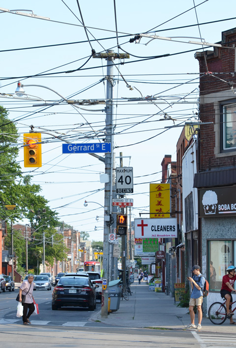 Broadview looking south from Gerrard with utility poles and lots of wires, people crossing the street, some traffic, the clears with the sign with a red cross on it