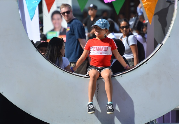 a young girl in a Canada T shirt sits in the O of the 3 D Toronto sign at Nathan Phillips square, people walking behind her, a man turns to look over his shoulder and appears to be looking at the girl