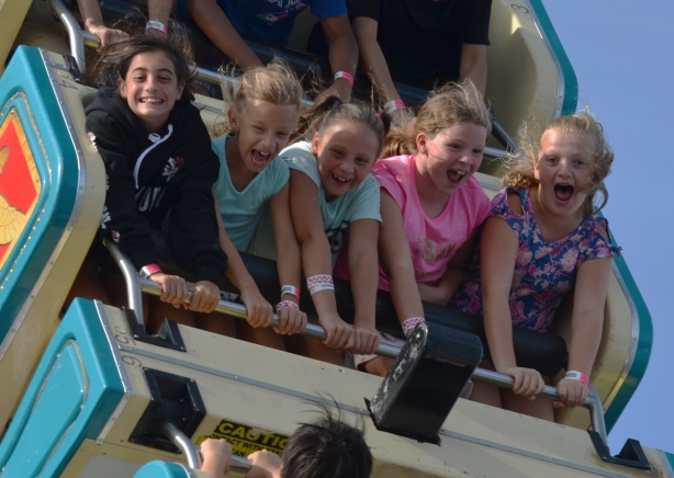 5 young girls screaming as they ride on a midway ride