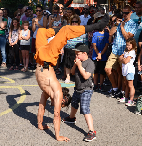 hiro son, a Japanese performance artist is standing on his hands in front of a young boy who has his hands close to his mouth, crowd watching in the background