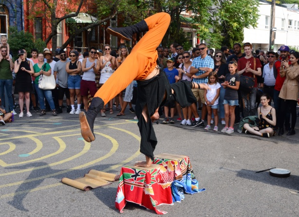 hiro son, a Japanese performance artist stands on one hand on a box in front of a crowd, outdoors, on the street, street performance