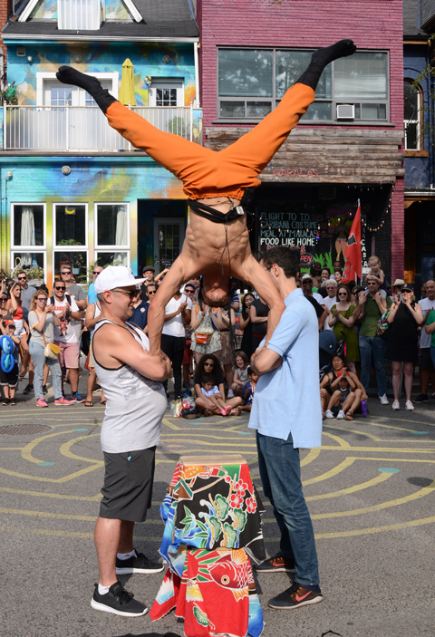 hiro son, a Japanese busker and performance artist does a hand stand on the arms of two men standing facing each other, orange sweat pants and legs open wide for balance, a crowd is watching from behind