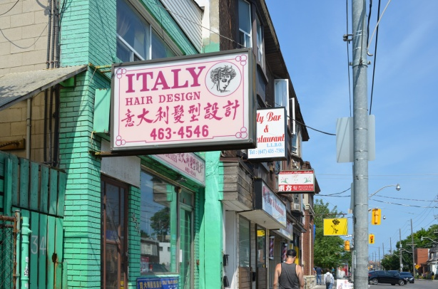 store fronts on Gerrard including one that is painted bright green, signs over the doors including the Italy hair design store with sign in English and Chinese