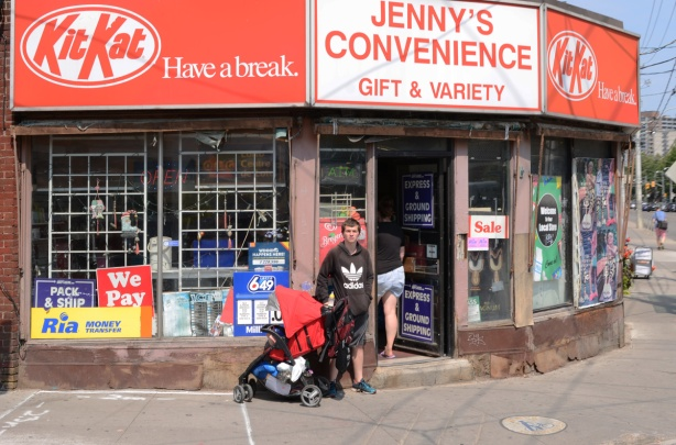 a young man stands beside a stroller outside Jenny's Convenience store on Parliament street, large red and white sign with kit kat logo on it twice - once at each end