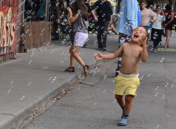 a young boy in yellow shhorts and blue shoes is laughing as he runs through a stream of bubbles, outside on the street
