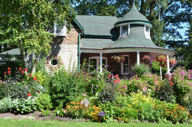Kew Williams house in Toronto, with small turret, and porch, gardens in front with lots of flowers