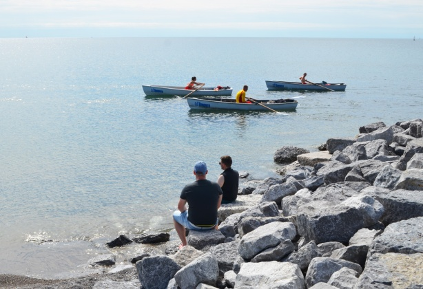 two men sit on rocks on the shore of Lake Ontario watching 3 life guard rowboats passing by